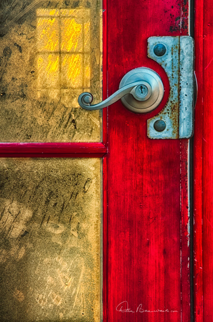 The red door on the front of Kitty Hawk Pier.  The golden light of dawn streams through the pier building, highlighting the condensation on the inside of the door glass.